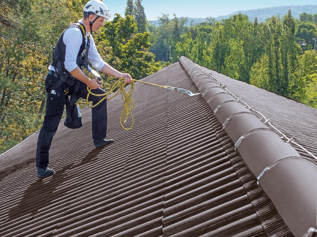 Mann mit angehängter Schutzausrüstung auf dem Dach.
