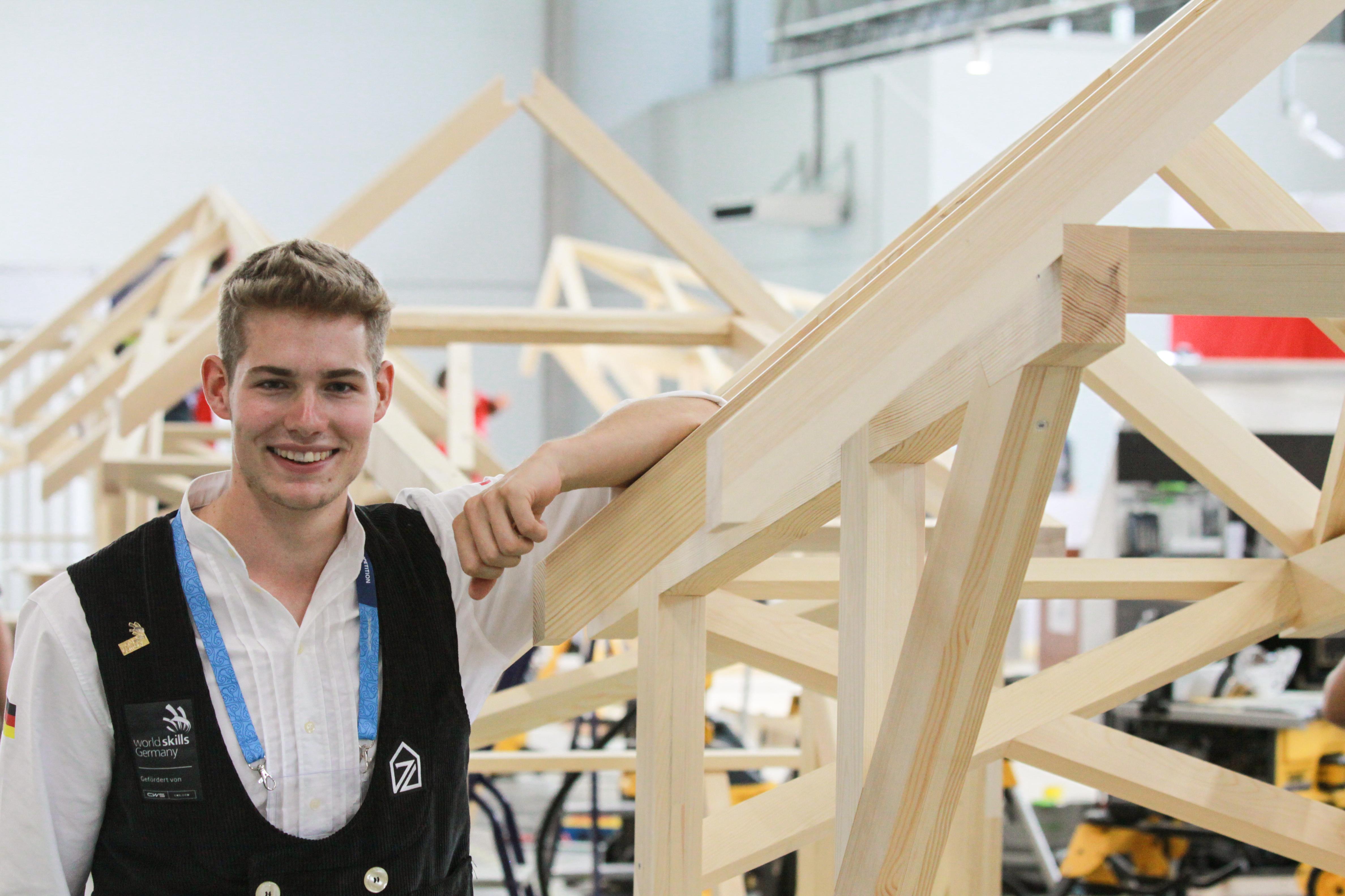 Weltmeister Alexander Bruns neben Holzaufbau