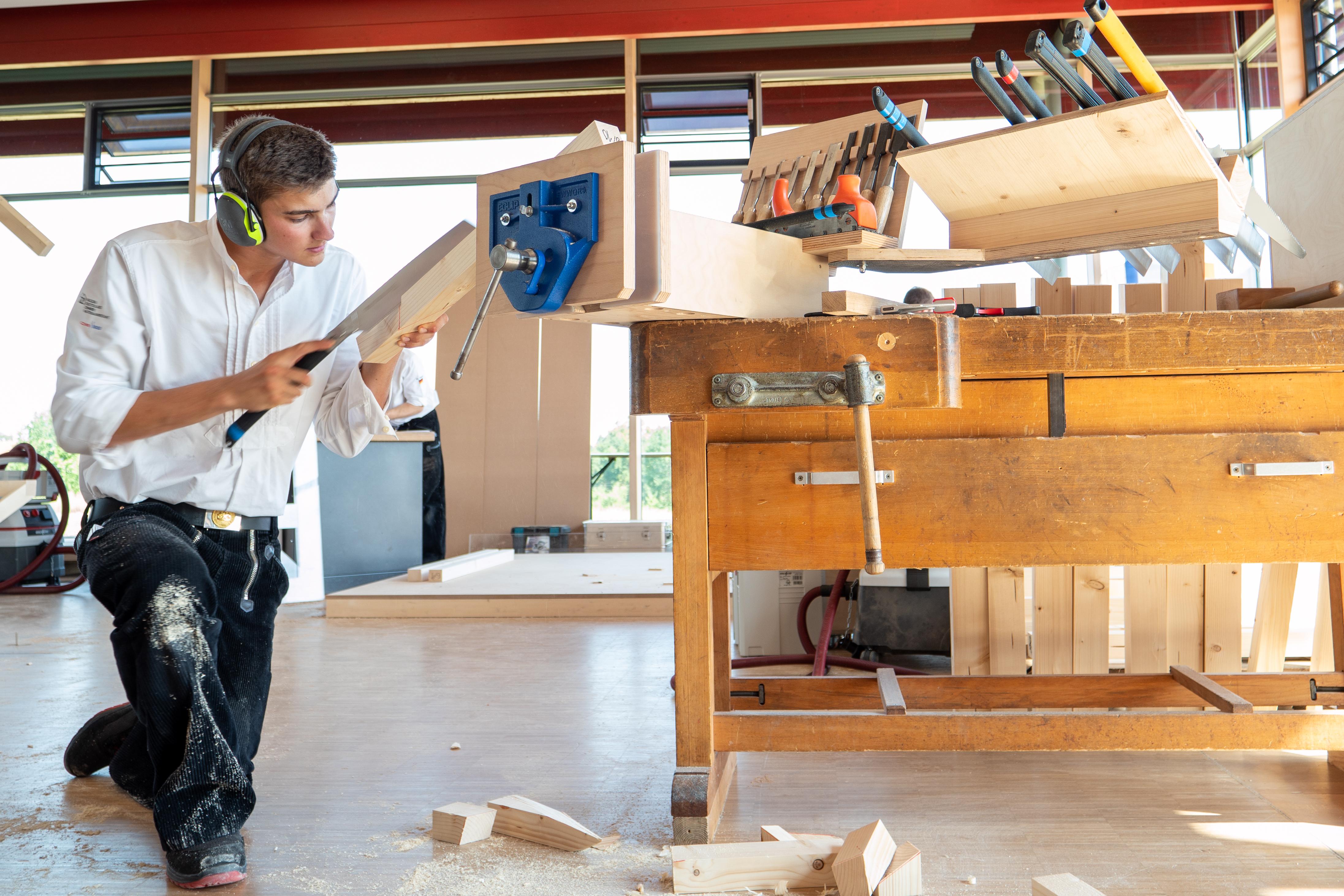 Junger Zimmerer konzentriert bei Holzbauarbeit