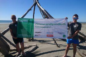 Max Moll und Miche Klinger halten Banner hoch mit Zimmererstipendium Neuseeland