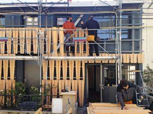 Zuschneidung der Holzverkleidung eines Einfamilienhauses