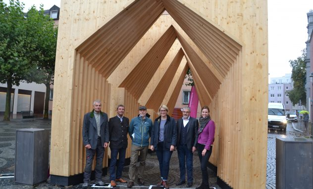 Sechs Menschen vor Holzbögen