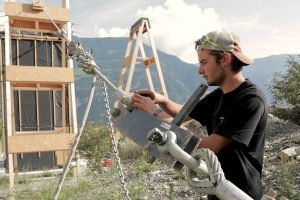 Junger Mann befestigt karabiner an Stahlseil vor einem Holzgebäude