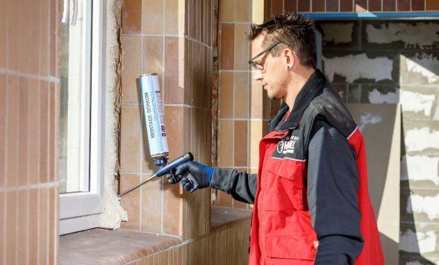Arbeiter mit roter Jacke versprüht PU-Schaum