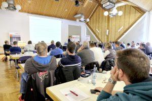 Gut gefüllte Vortragshalle mit Leinwandpräsentation