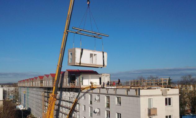 Holzmodul wird auf bestehendes Gebäude mit Kran gesetzt.
