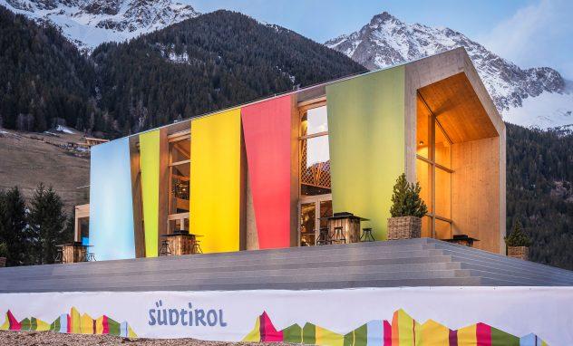 Buntes Haus vor Alpenkulisse