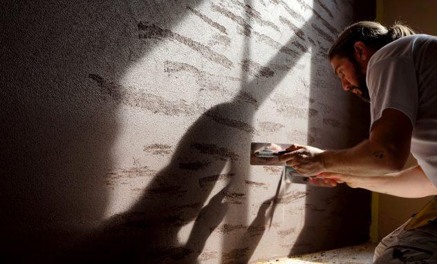 Handwerker vor Lehmwand