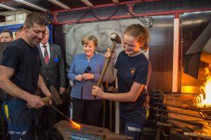 Kanzlerin Merkel umrahmt von Handwerkern