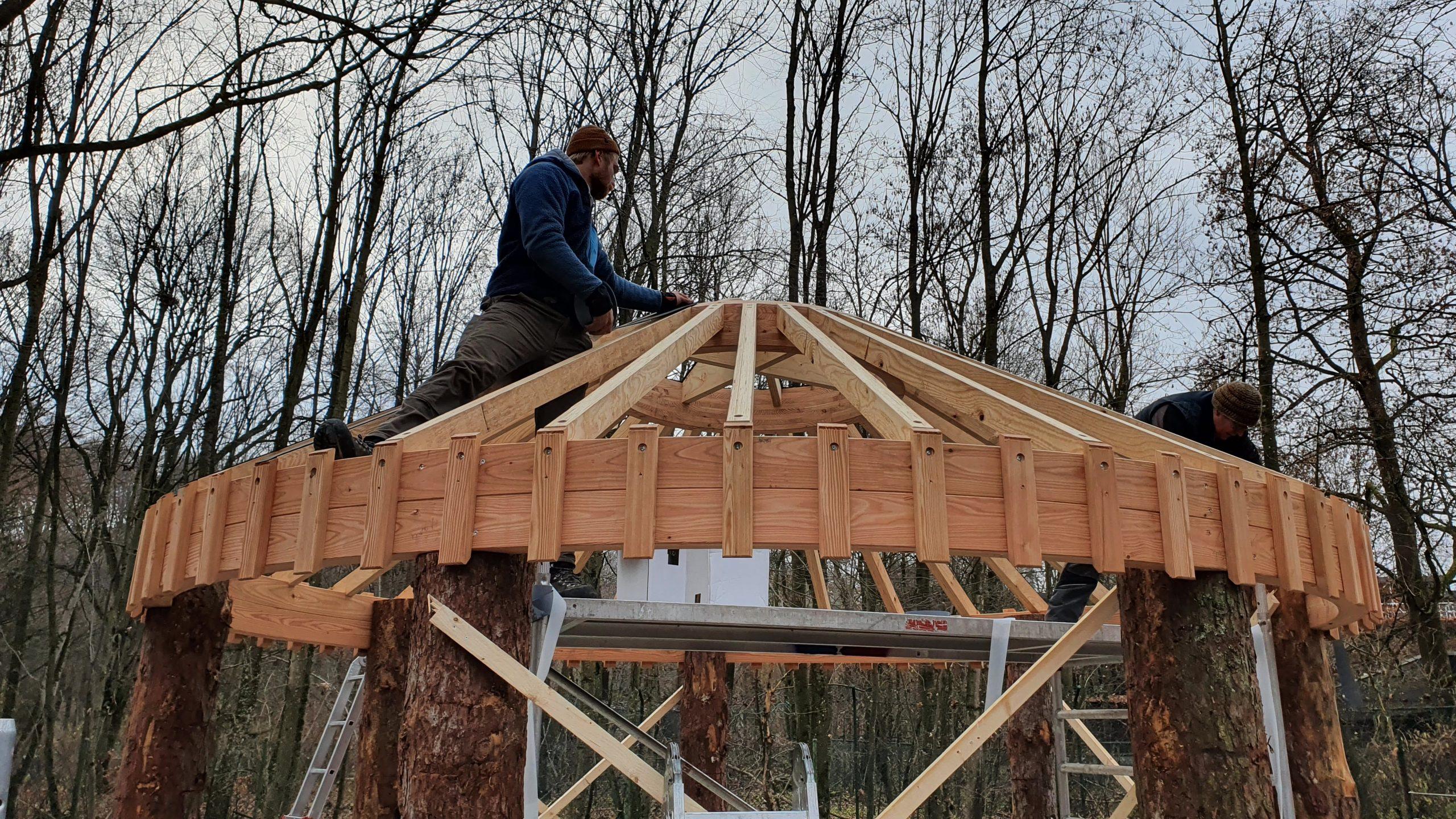 Mann auf Holzdach